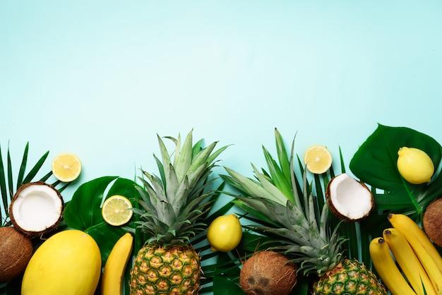 Exotische ananas, reife kokosnüsse, bananen, melonen, zitronen, tropische palmen und grüne monsterblätter Premium Fotos