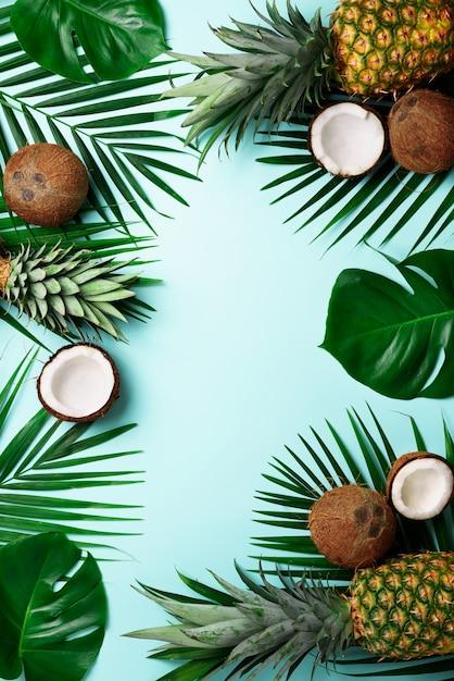 Exotische ananas, reife kokosnüsse, tropische palmen und grüne monsterblätter Premium Fotos