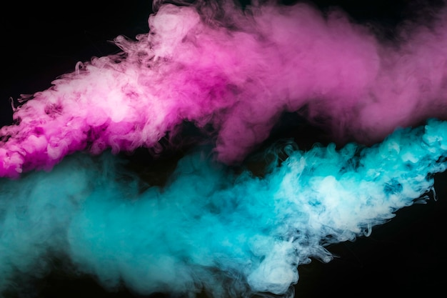 Explosion des blauen und rosafarbenen rauches gegen schwarzen hintergrund Kostenlose Fotos