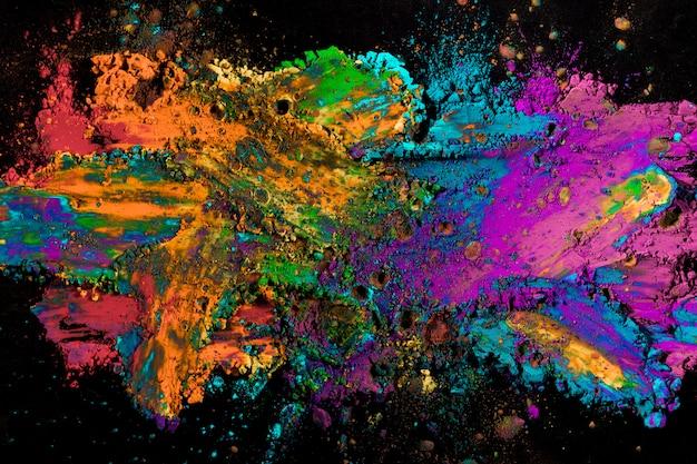 Explosion des farbigen pulvers auf schwarzer oberfläche Kostenlose Fotos