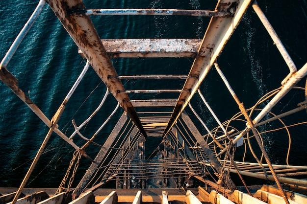 Extrem alte und auseinandergerissene treppe, die von einer alten brücke zum welligen meer hinunterführt Kostenlose Fotos