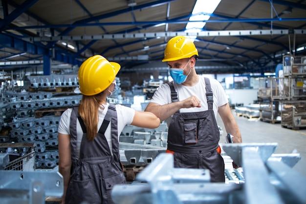 Fabrikarbeiter begrüßen sich gegenseitig mit ellbogen während der koronavirus-pandemie Kostenlose Fotos