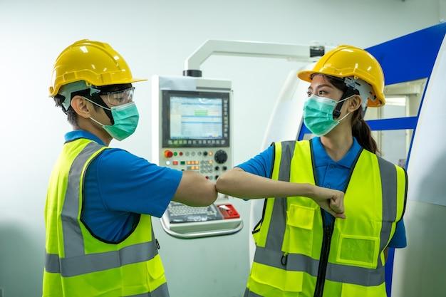 Fabrikarbeiter, der schützende gesichtsmasken trägt, die stoßende ellbogen in der fabrik begrüßen Premium Fotos