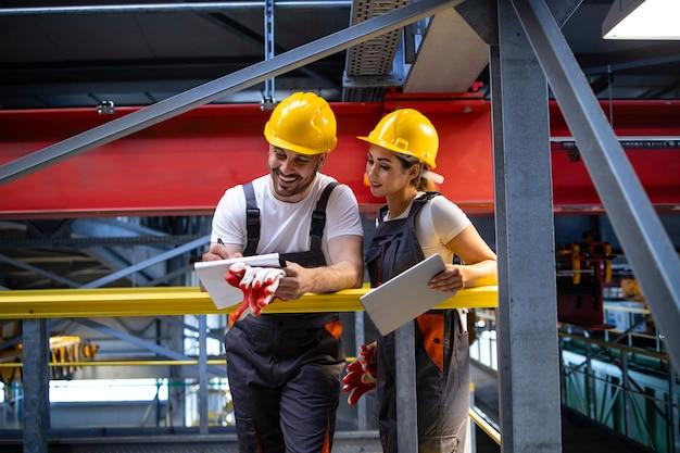 Fabrikarbeiter in schutzausrüstung stehen in der produktionshalle und tauschen ideen aus Kostenlose Fotos