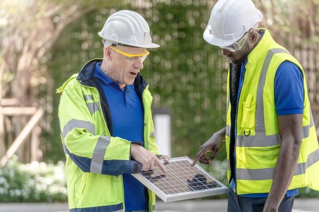 Fabrikarbeiter techniker ingenieur männer überprüfen solarzellen-panel auf nachhaltige technologie mit grünem arbeitsanzug kleid und schutzhelm. Premium Fotos