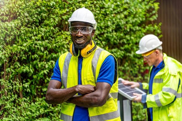Fabrikarbeiter techniker ingenieur mann stehendes vertrauen mit grünem arbeitssuite kleid und schutzhelm im vorderen arbeiter, der solarzellenpanel prüft Premium Fotos