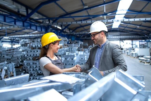 Fabrikleiter besucht die produktionslinie und gratuliert dem arbeiter zu harter arbeit und guten ergebnissen Kostenlose Fotos