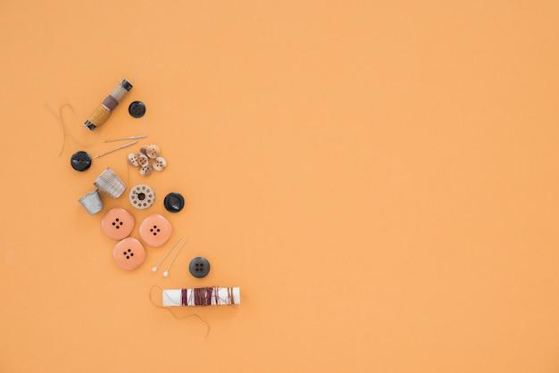 Faden; nadel; fingerhut und verschiedene knöpfe auf farbigem hintergrund Kostenlose Fotos