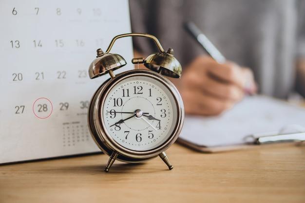 Fälligkeitsdatum kalender und business-frau arbeiten Premium Fotos