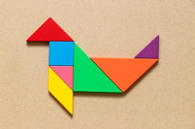 Färben sie tangrampuzzlespiel in der dichtungs- oder seelöwenform auf hölzernem hintergrund Premium Fotos