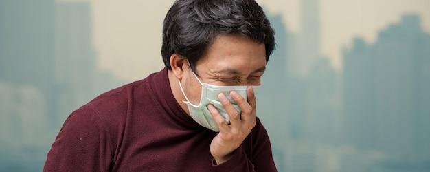 Fahne des asiatischen mannes die gesichtsmaske gegen luftverschmutzung tragend Premium Fotos