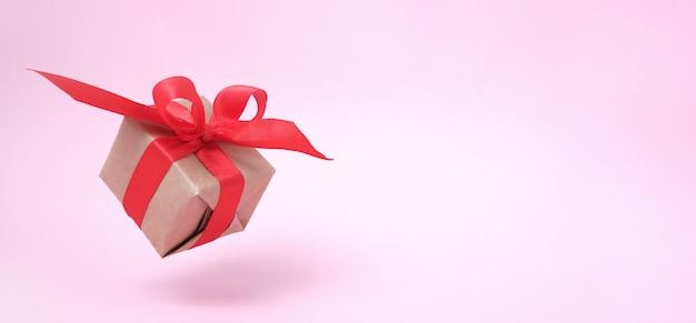 Fahne mit rotem band der geschenkbox auf rosa. Premium Fotos