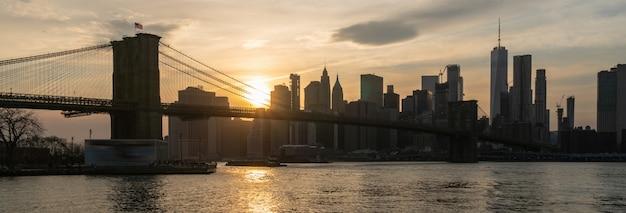Fahnen- und abdeckungsszene von new york cityscape mit brooklyn-brücke über dem east river bei dem sonnenuntergang Premium Fotos