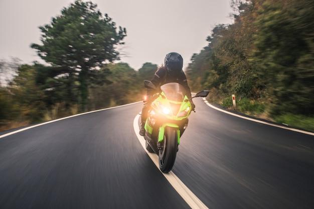 Fahren des grünen neonfarbmotorrades auf der straße, vorderansicht. Kostenlose Fotos