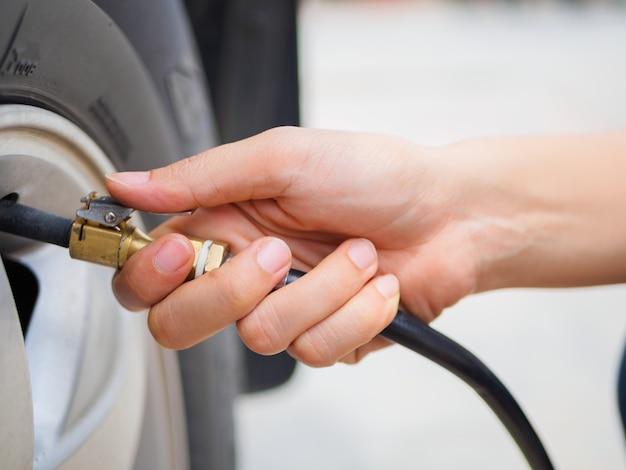 Fahrer, der luftdruck überprüft und luft in den reifen füllt. Premium Fotos