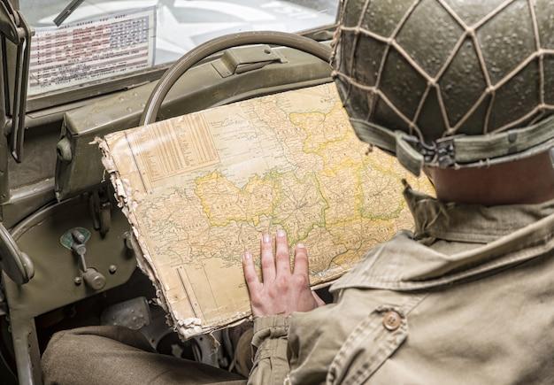 Fahrer eines militärfahrzeugs blick auf eine karte der normandie Premium Fotos