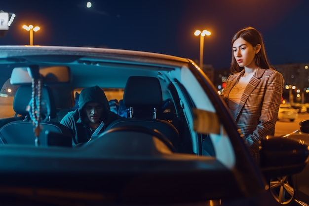 Fahrerin am auto, einbrecher auf dem rücksitz, verbrecher, diebstahl. Premium Fotos