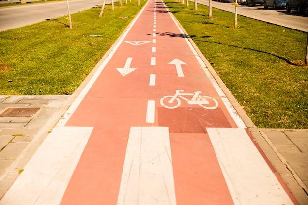 Fahrradweg mit zeichen zwischen dem grünen gras Kostenlose Fotos