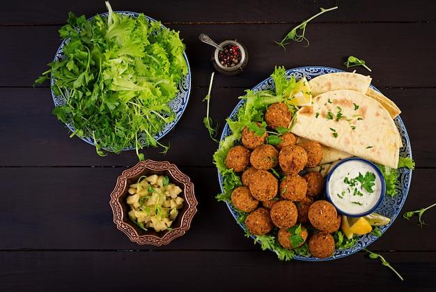 Falafel, hummus und pita. orientalische oder arabische gerichte auf dunkel Premium Fotos