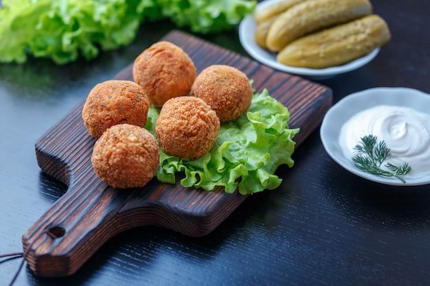 Falafel liegt auf einem holzbrett. auf dem tisch liegen tomaten, gurken, salat, dill, zitrone, sauerrahm. naher osten nationalgericht. Premium Fotos