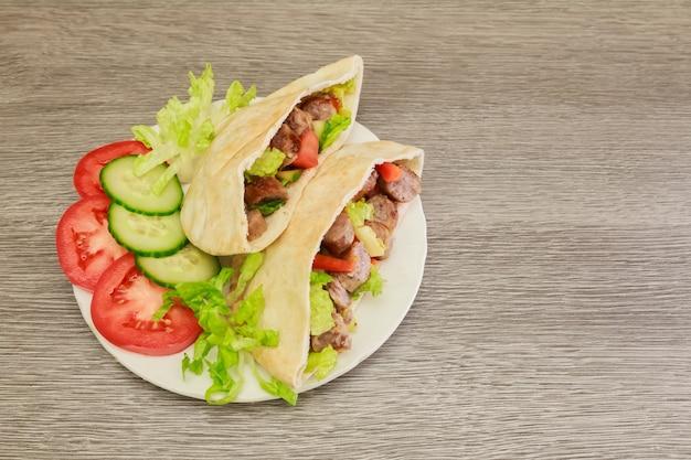 Falafel und frischgemüse im pittabrot auf hölzernem Premium Fotos