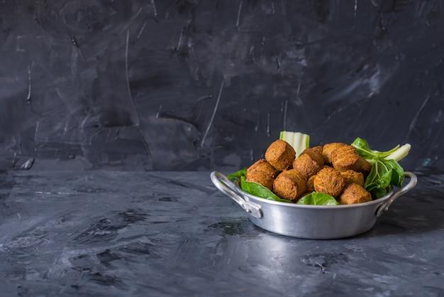 Falafelbälle dienten in der platte mit grünen blättern auf hölzernem schwarzem hintergrund Premium Fotos