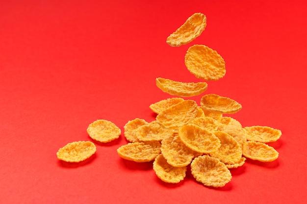 Fallende cornflakes lokalisiert auf rotem farbhintergrund, stapel des traditionellen frühstücksflocken, volle schärfentiefe Premium Fotos