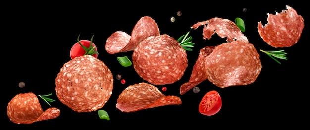 Fallende geschnittene salami isoliert auf schwarzraum Premium Fotos