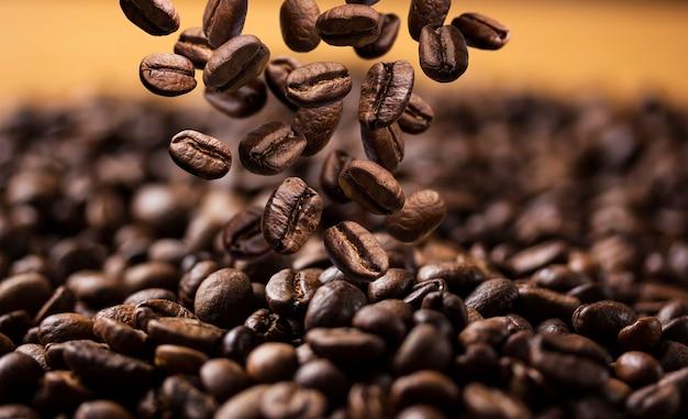 Fallende röstkaffeebohnen auf dunkler oberfläche Premium Fotos