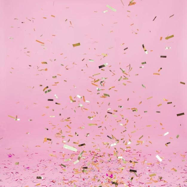 Fallender goldener confetti auf rosa hintergrund Kostenlose Fotos