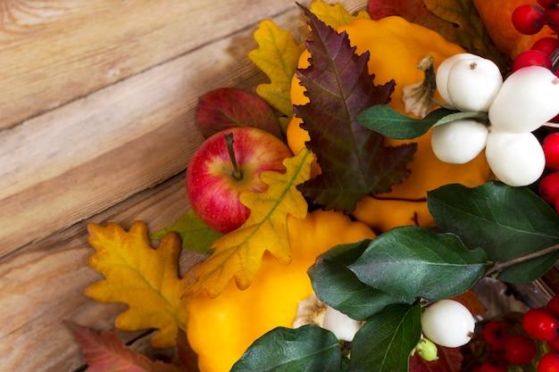 Fallhintergrund mit snowberry und gelbem kürbis Premium Fotos