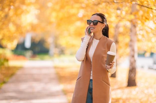 Fallkonzept - trinkender kaffee der schönheit im herbstpark unter herbstlaub Premium Fotos