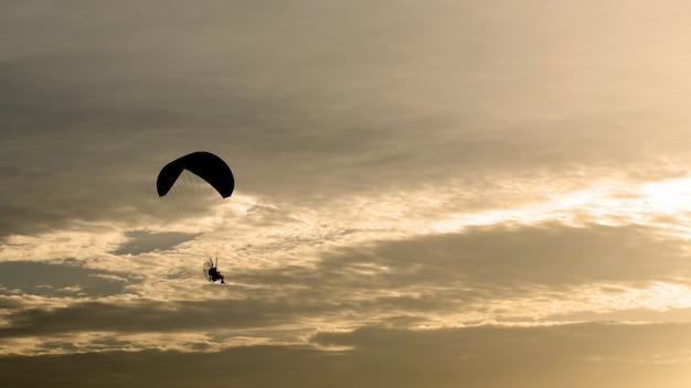 Fallschirm- oder motorschirmfliege im sonnenuntergang, schwarzer schatten, sportaktivität Premium Fotos
