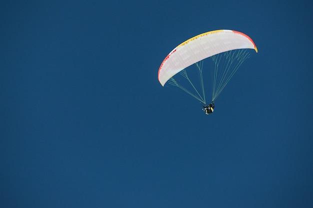 Fallschirmspringer unter einem baldachin eines fallschirms gegen einen blauen himmel in georgia, gudauri Premium Fotos