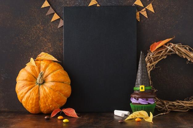 Falltafelhintergrund mit kürbis- und halloween-leckereien Premium Fotos