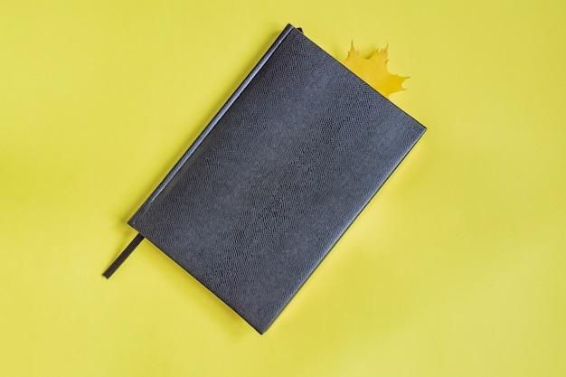 Falsches ledernotizbuch der schwarzen farbe mit ahornblatt als bookmark auf gelb. Premium Fotos