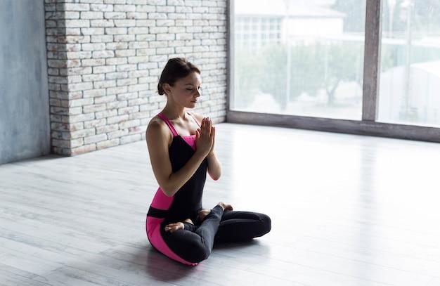 Faltende hände der frau in der namaste yogahaltung beim sitzen Kostenlose Fotos