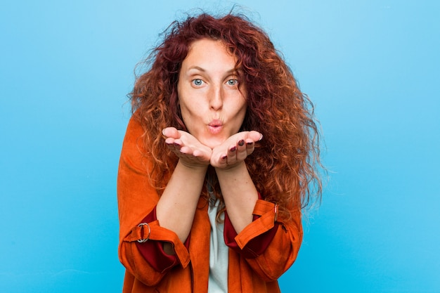 Faltende lippen der eleganten frau der jungen rothaarigen und halten von palmen, um luftkuss zu senden. Premium Fotos