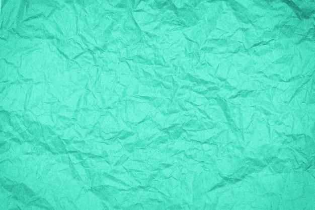 Faltige papierbeschaffenheit des abstrakten verpackungshandwerks, hintergrund, getönt in biskaya-grün Premium Fotos