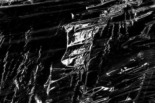 Faltige plastikfolientextur auf einer schwarzen tapete Kostenlose Fotos