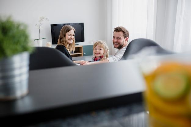 Familie auf dem sofa, das kamera betrachtet Kostenlose Fotos