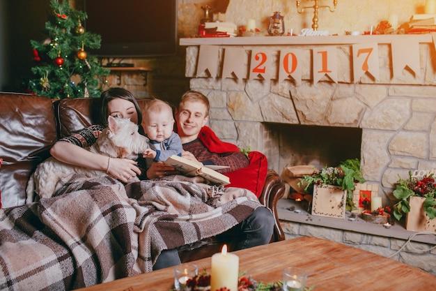 familie auf dem sofa mit einer decke zugedeckt liegen w hrend sie auf ein buch schauen und auf. Black Bedroom Furniture Sets. Home Design Ideas