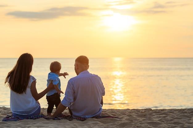 Familie auf dem strandkonzept, kaukasischer junge, der sand auf dem tropischen strand in der sonnenuntergangzeit stationiert und hält Premium Fotos