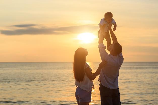 Familie auf dem strandkonzept, vater, der seinen sohn auf dem tropischen strand spielt und trägt Premium Fotos