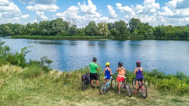 Familie auf den fahrrädern, die draußen, eltern und kinder auf fahrrädern, luftdraufsicht der glücklichen familie radfahren Premium Fotos