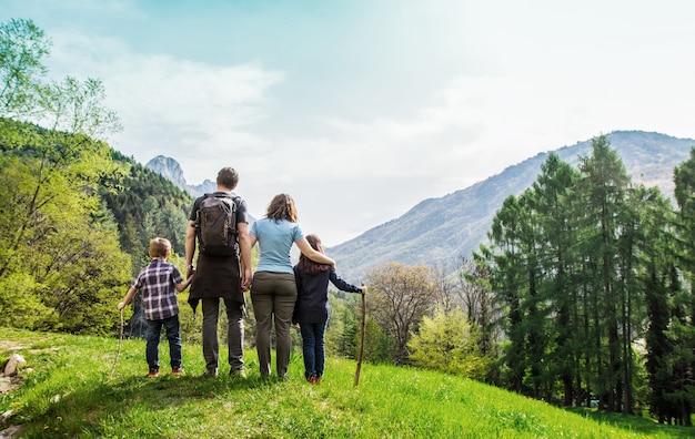 Familie auf einer grünen wiese mit blick auf das bergpanorama Premium Fotos