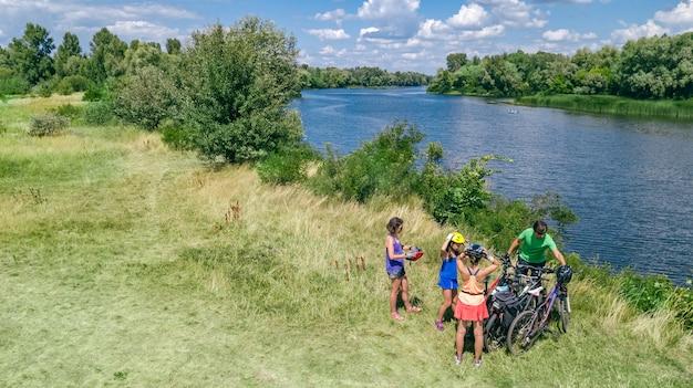 Familie auf fahrrädern draußen radfahrend, aktive eltern und kinder auf fahrrädern, luftdraufsicht der glücklichen familie mit den kindern, die sich nahe entspannen Premium Fotos