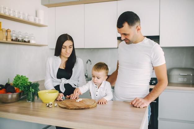 Familie bereiten den salat in einer küche zu Kostenlose Fotos