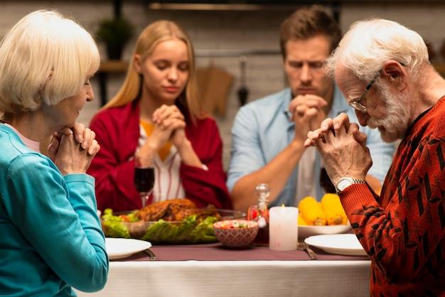 Familie, die an der vorderansicht des abendtisches betet Kostenlose Fotos