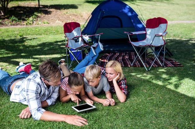 Familie, die auf gras liegt und digitale tablette verwendet Premium Fotos